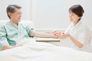 シニア男性の脈を計る看護師の写真素材 [FYI01479969]