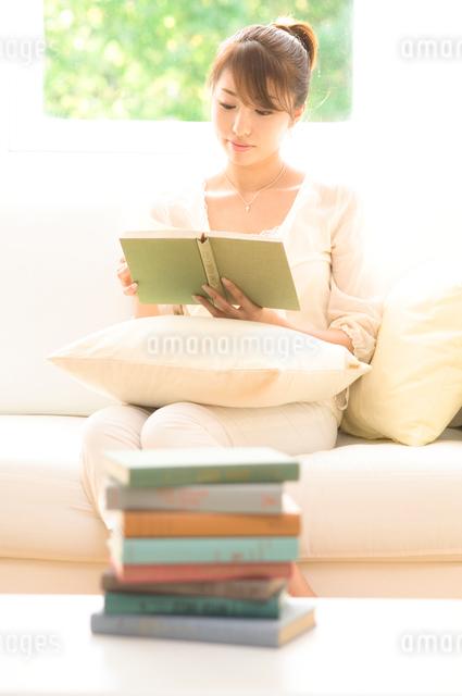 ソファに座り読書する女性の写真素材 [FYI01480029]