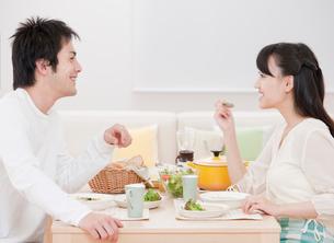 ダイニングテーブルで食事を楽しむ新婚夫婦 ダイニングの写真素材 [FYI01480054]