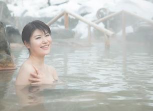 雪と露天風呂に入る20代女性の写真素材 [FYI01480056]