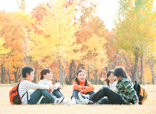 紅葉の中で遠足を楽しむ小学生の写真素材 [FYI01480072]