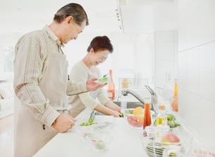 キッチンで料理をするシニア夫婦の写真素材 [FYI01480146]