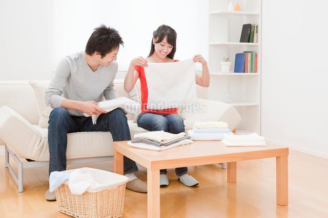洗濯物をたたむ新婚夫婦 リビングの写真素材 [FYI01480153]