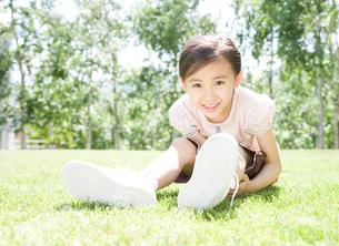 新緑と芝生に座る女の子の写真素材 [FYI01480157]