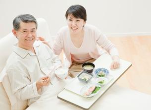 ベッドで食事をする父親と娘の写真素材 [FYI01480162]