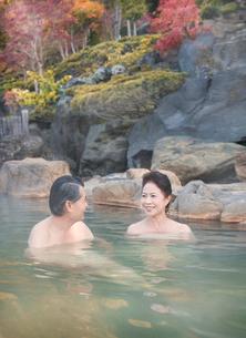 露天風呂に入る60代の夫婦と紅葉の写真素材 [FYI01480190]