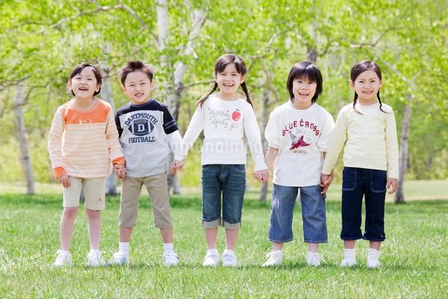 新緑の中で手をつなぐ5人の子供の写真素材 [FYI01480199]