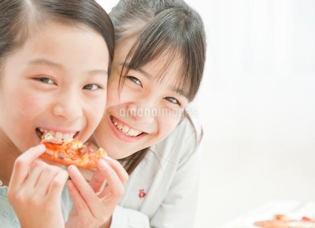 ピザを食べる小学生の女の子の写真素材 [FYI01480207]
