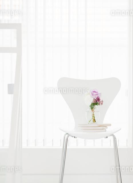 椅子の上に置かれた本と花瓶の写真素材 [FYI01480232]