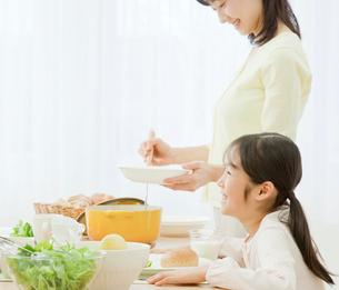 ダイニングテーブルで食事をする家族の写真素材 [FYI01480238]
