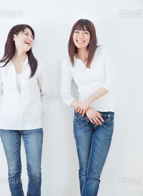 会話する2人の20代女性のポートレート/白バックの写真素材 [FYI01480253]