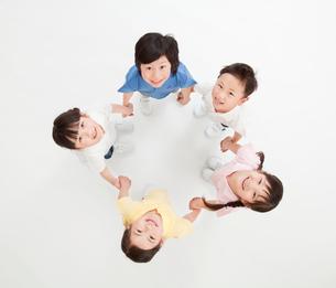 輪になって手をつなぐ5人の子供 俯瞰の写真素材 [FYI01480257]