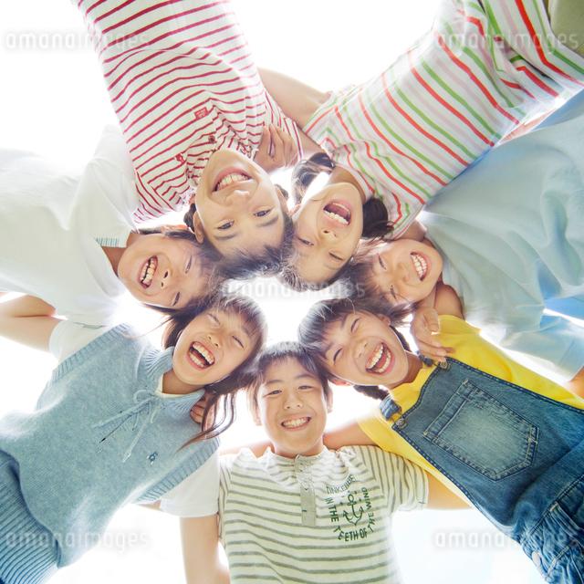 肩を組み輪になる7人の小学生の男の子と女の子の写真素材 [FYI01480258]