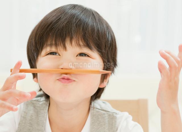 鼻と口の間に鉛筆をはさむ男の子の写真素材 [FYI01480295]