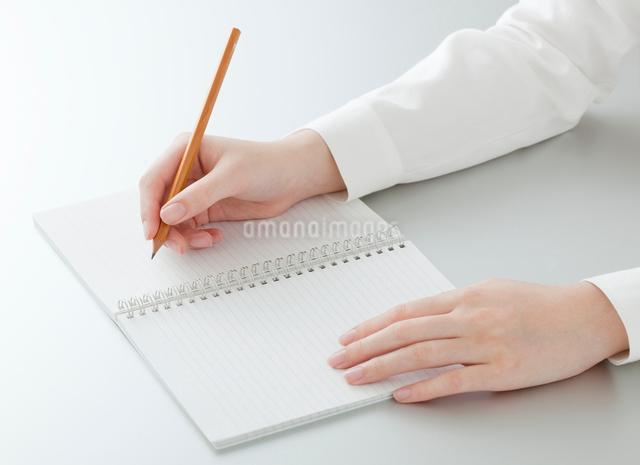 ノートに書きこむ女性の手の写真素材 [FYI01480296]