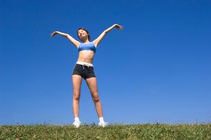青空のもとで伸びをする女性の写真素材 [FYI01480297]