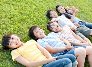 芝生に寝転ぶ5人の小学生の男の子と女の子の写真素材 [FYI01480325]