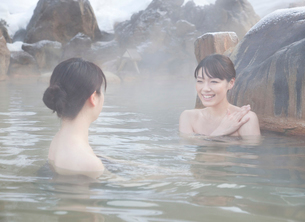 雪と露天風呂に入る2人の20代女性の写真素材 [FYI01480335]