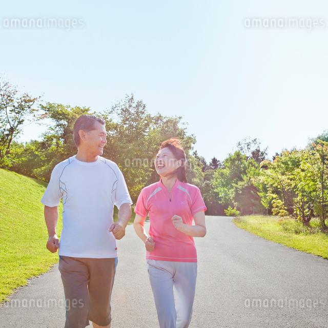 ウォーキングするトレーニングウェアの60代シニア夫婦の写真素材 [FYI01480388]