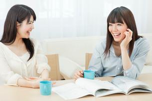 カタログを見ながら会話を楽しむ2人の20代女性の写真素材 [FYI01480412]