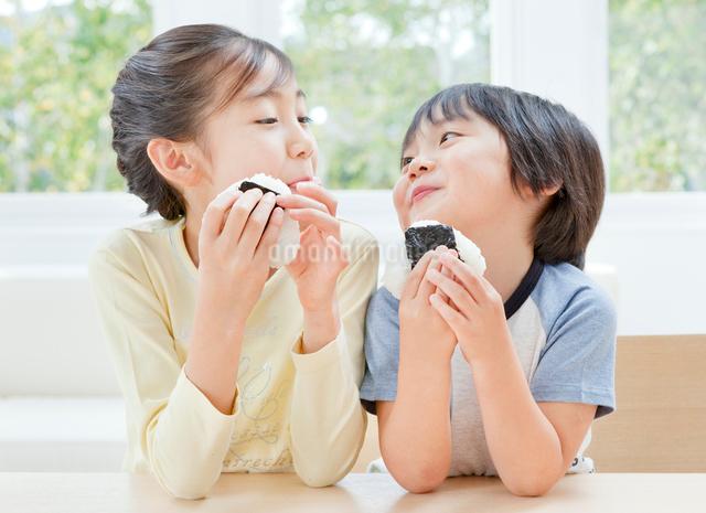 おにぎりを食べる女の子と男の子の姉弟の写真素材 [FYI01480434]