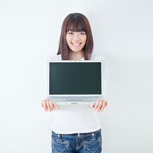ノートパソコンを持つ20代女性のポートレート/白バックの写真素材 [FYI01480445]
