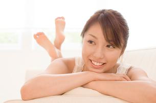 ソファーに寝ころぶ女性の写真素材 [FYI01480455]