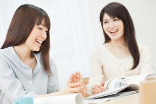 カタログを見ながら会話を楽しむ2人の20代女性の写真素材 [FYI01480460]