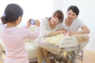 デジタルカメラで両親と赤ちゃんの写真を撮る子 リビングの写真素材 [FYI01480470]