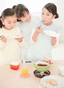 チョコレートフォンデュを楽しむ女の子の写真素材 [FYI01480498]