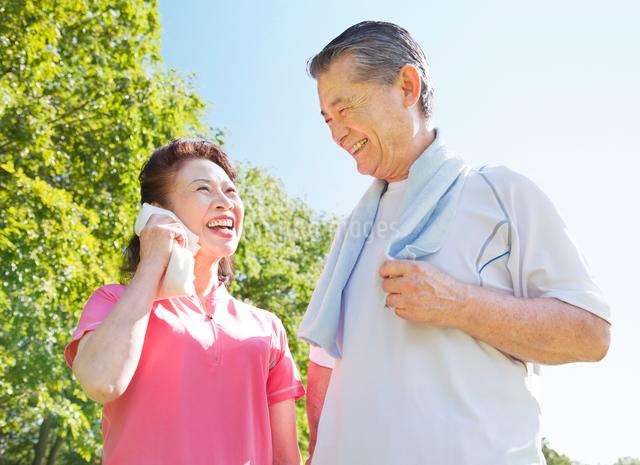 緑の中で笑うトレーニングウェアの60代シニア夫婦の写真素材 [FYI01480505]