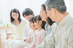 ソファーで団らんする三世代家族の写真素材 [FYI01480527]