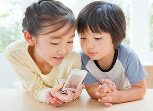 携帯電話を見る女の子と男の子の姉弟の写真素材 [FYI01480531]