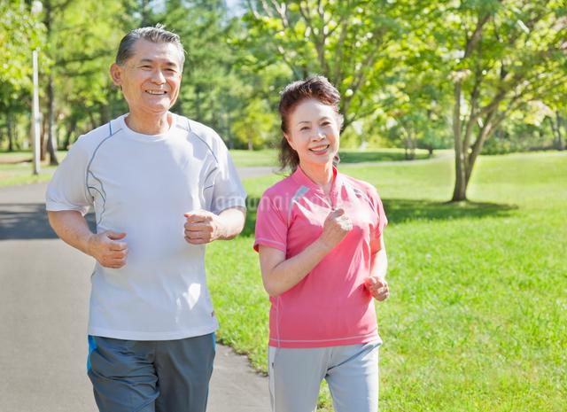 緑の中でジョギングするトレーニングウェアの60代シニア夫婦の写真素材 [FYI01480541]