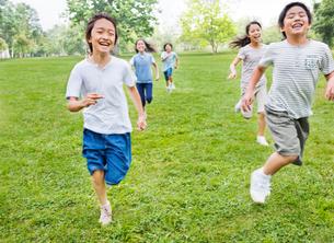 緑の中を走る小学生の男の子と女の子の写真素材 [FYI01480572]