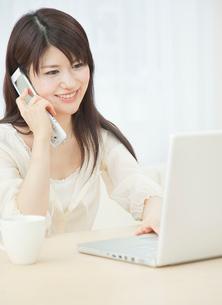 ノートパソコンと携帯電話を操作する20代女性の写真素材 [FYI01480590]