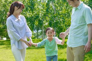 新緑の中を走る家族の写真素材 [FYI01480627]