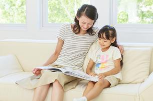 ソファーで本を読む母子の写真素材 [FYI01480628]