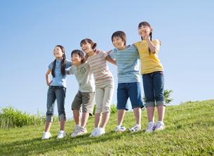 青空のもと肩を組む5人の小学生の写真素材 [FYI01480673]