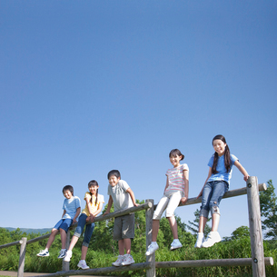 青空のもと木の柵に腰掛ける5人の小学生の写真素材 [FYI01480680]