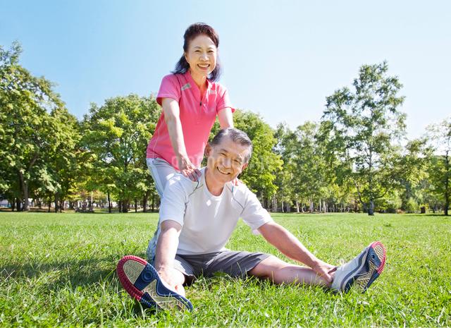 緑の中でストレッチをする60代シニア夫婦の写真素材 [FYI01480691]