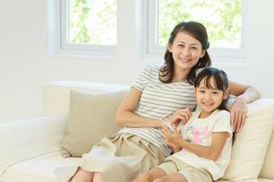 ソファーでスマートフォンを操作する母子の写真素材 [FYI01480694]