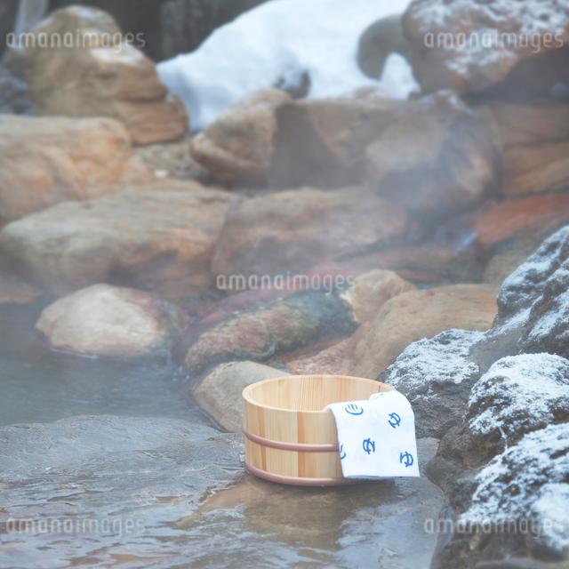 桶と手ぬぐい 雪の温泉イメージの写真素材 [FYI01480695]