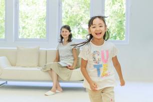 リビングを走る女の子とソファから見守る母親の写真素材 [FYI01480696]