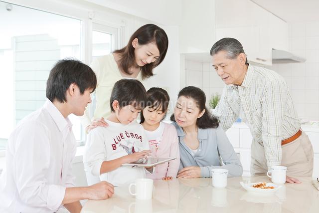 リビングでiPadを操作する三世代家族の写真素材 [FYI01480722]