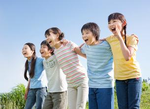 青空のもと肩を組む5人の小学生の写真素材 [FYI01480727]
