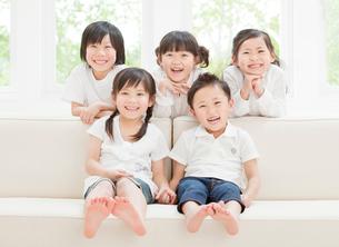 ソファーに集まる5人の子供の写真素材 [FYI01480744]