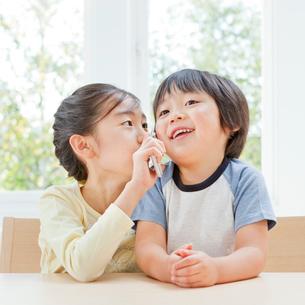 携帯電話で話す女の子と男の子の姉弟の写真素材 [FYI01480763]