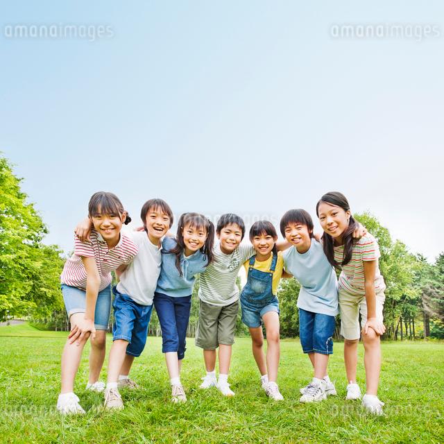 緑の中で肩を組む7人の小学生の男の子と女の子の写真素材 [FYI01480776]