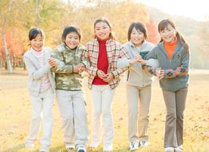 紅葉の中にいる仲の良い小学生の写真素材 [FYI01480790]
